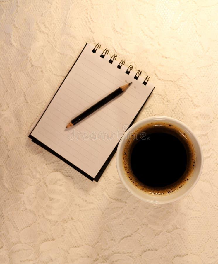 Een kop van zwarte koffie, notitieboekje en een grafietpen met twee scherpe einden stock afbeeldingen