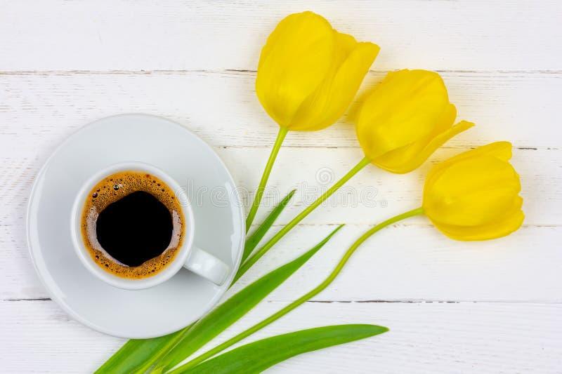 Een Kop van zwarte koffie op een schotel en een gele Tulp drie bloeien op een witte houten close-up als achtergrond, hoogste meni stock foto