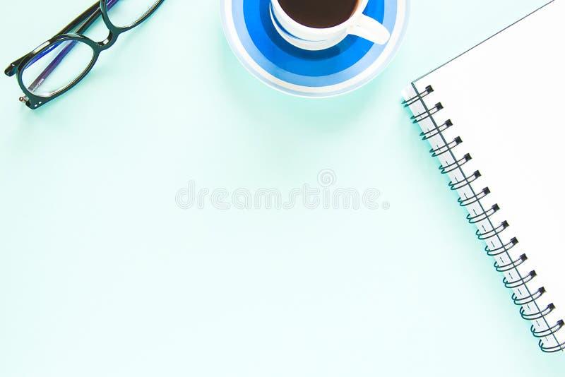 Een kop van zwarte koffie, een open nota met witte pagina, glazen op een pastelkleur blauwe achtergrond De ruimte van het exempla stock foto's