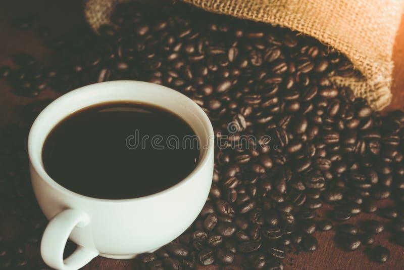 Een kop van zwarte koffie in witte kop met koffieboon in zakrug royalty-vrije stock fotografie