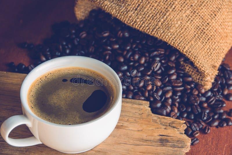 Een kop van zwarte koffie in witte kop met koffieboon in zakzak royalty-vrije stock afbeeldingen