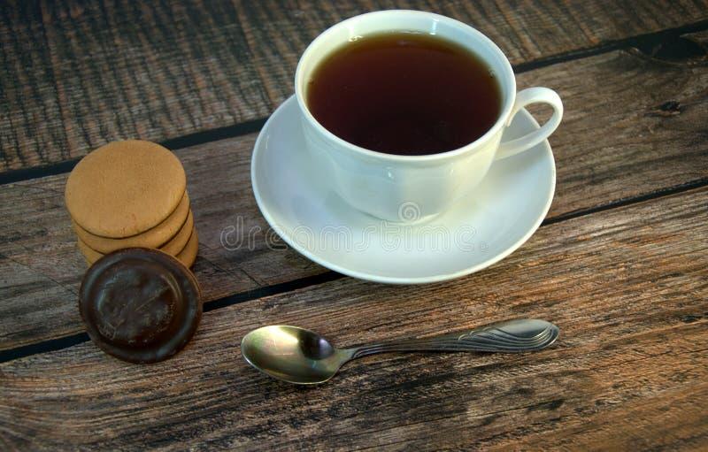 Een kop van zwarte thee op een porseleinschotel, een lepel en een stapel sponskoekjes met chocolade, ligt op een houten lijst royalty-vrije stock foto