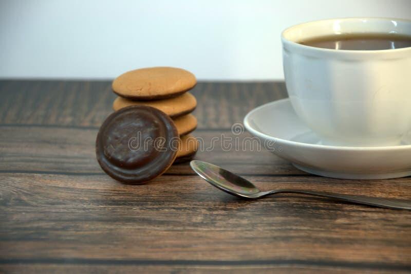 Een kop van zwarte thee op een porseleinschotel, een lepel en een stapel sponskoekjes met chocolade, ligt op een houten lijst royalty-vrije stock fotografie