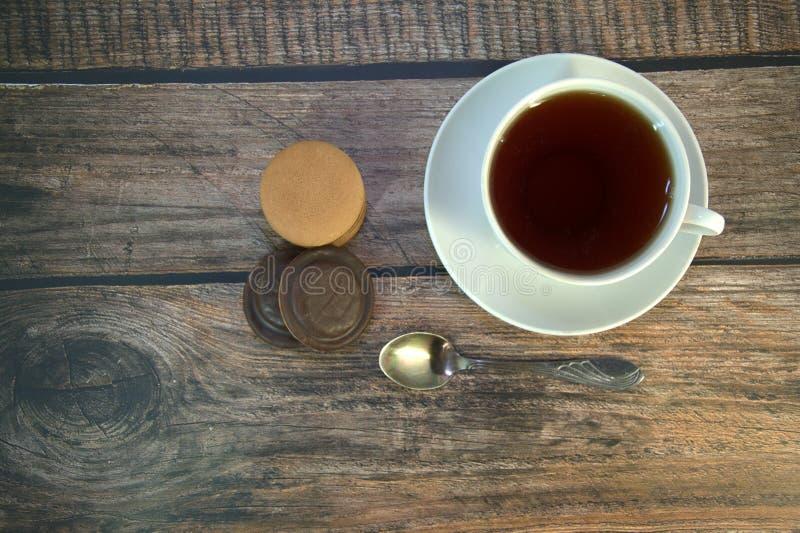 Een kop van zwarte thee op een porseleinschotel, een lepel en een stapel sponskoekjes met chocolade, ligt op een houten lijst royalty-vrije stock foto's