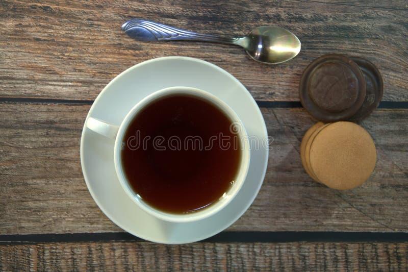 Een kop van zwarte thee op een porseleinschotel, een lepel en een stapel sponskoekjes met chocolade, ligt op een houten lijst stock foto's