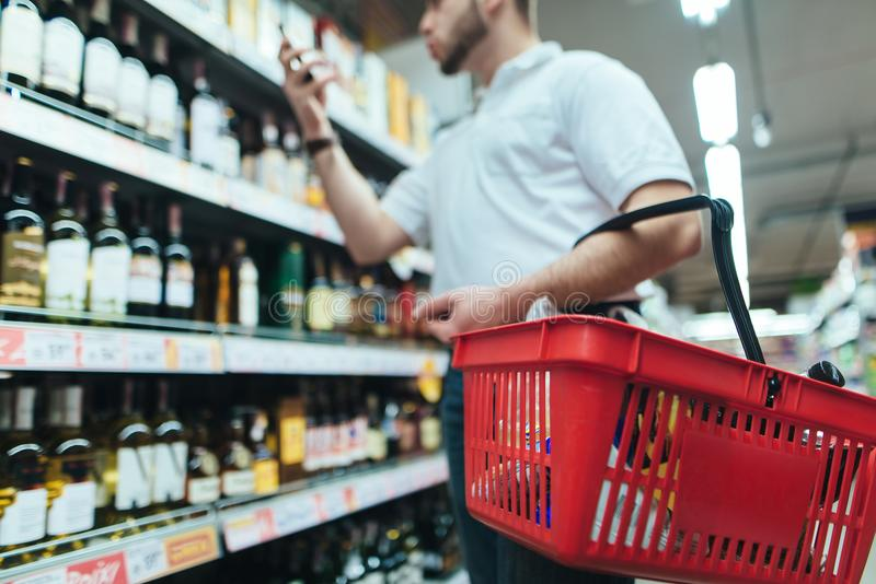 Een koper met een rode wijnmand kiest wijn in de alcoholopslag van de opslag De keus van goederen in de supermarkt stock afbeeldingen