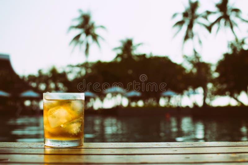 Een kort glas ijsbier bij pool royalty-vrije stock foto's