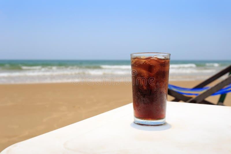 Een koude drank in een glas op het strand, stock afbeeldingen