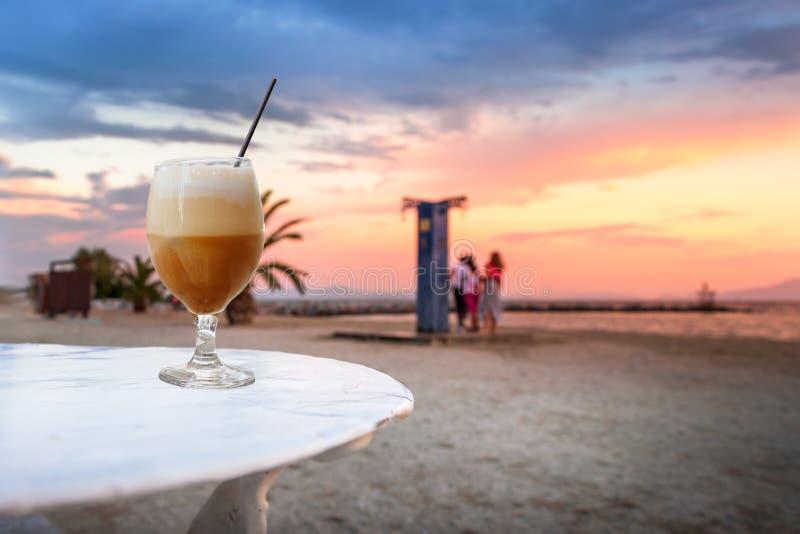 Een koude koffie van de freddocappuccino bij het strand bij zonsondergang in Volos, royalty-vrije stock afbeelding