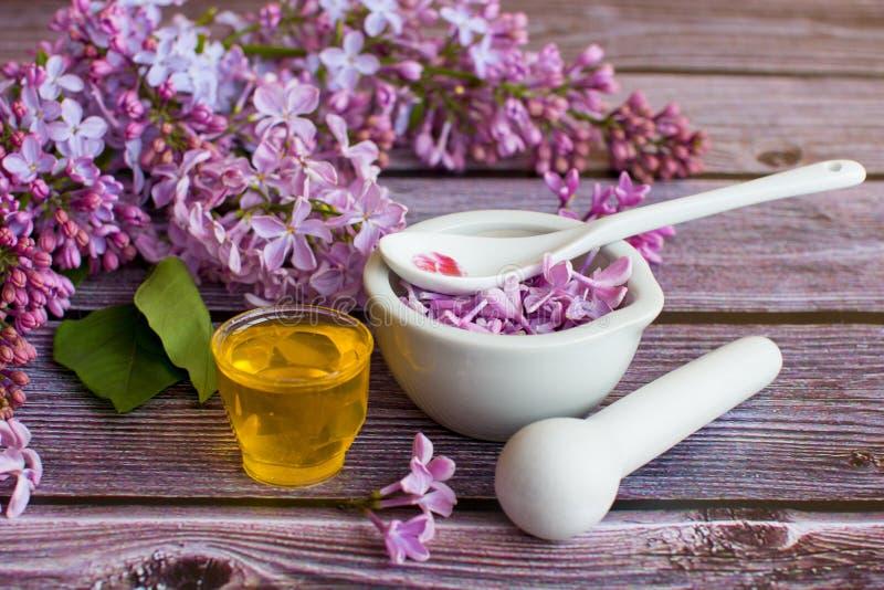 een kruik geurige bloemhoning Bewaarde honing en lilac bloemen stock foto's