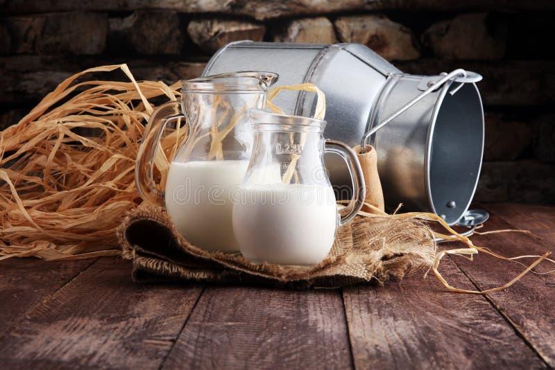 Een kruik melk en glas melk op een houten lijst royalty-vrije stock afbeeldingen