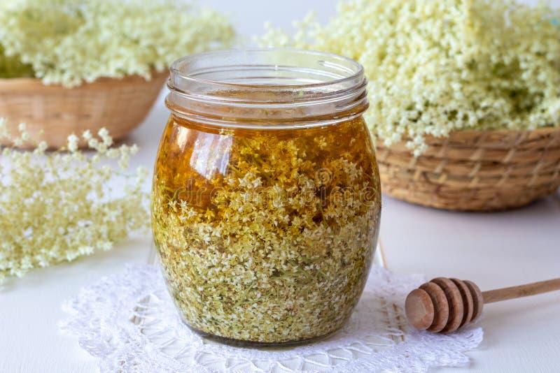 Een kruik met verse oudere bloemen en honing wordt gevuld, syru voor te bereiden die stock afbeelding