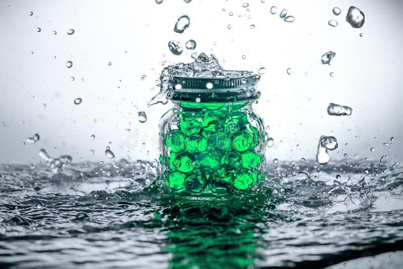 Een kruik van gelparels met waterplonsen stock fotografie