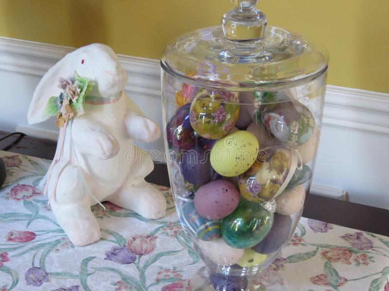 Een kruik van multicolored fauxeieren en een vals wit konijn voor een decoratie? stock foto's
