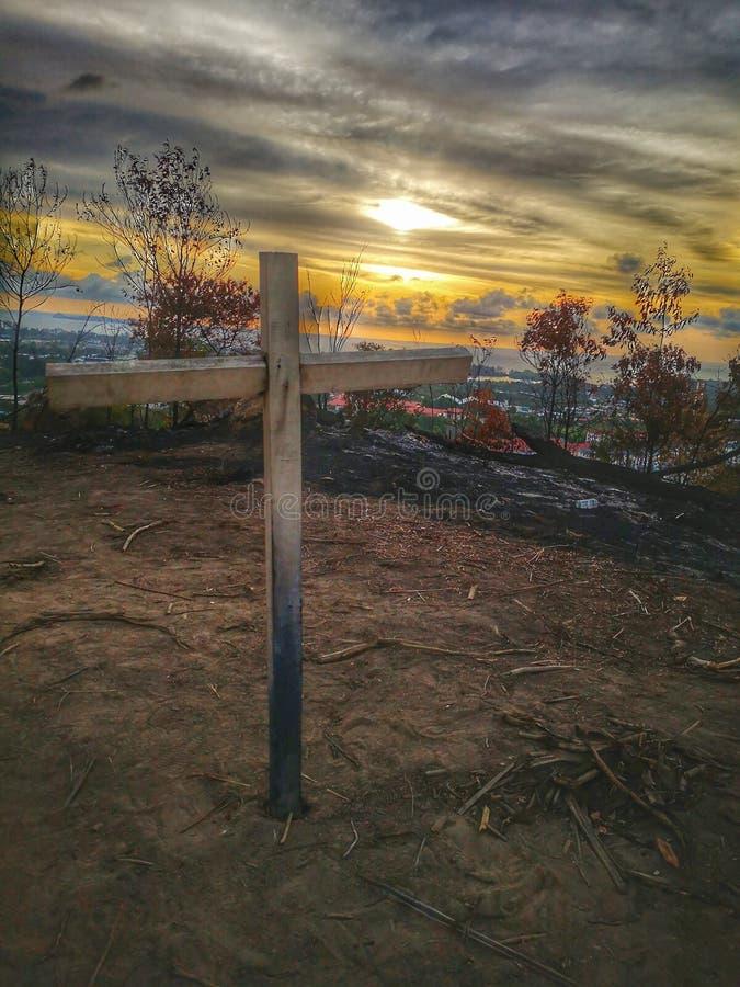 Een kruis op de bovenkant van de heuvel vóór de zonsondergangdaling stock foto's