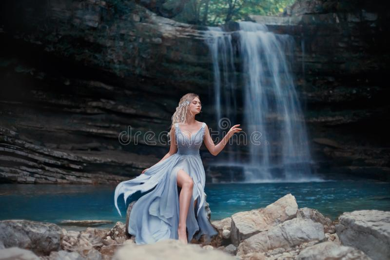 Een krullend blondemeisje in een luxueuze blauwe kleding zit op witte stenen tegen de achtergrond van een fabelachtig landschap R royalty-vrije stock afbeeldingen