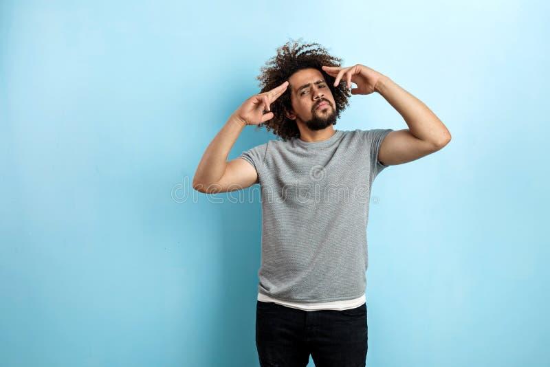 Een krullend-geleide knappe mens die een grijze T-shirt dragen bevindt zich met een geconcentreerde blik en met zijn die handen a stock afbeelding