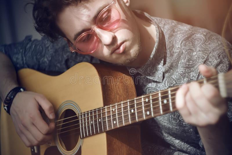 Een krullend-haired kerel met roze glazen speelt een houten akoestische gitaarmelodie royalty-vrije stock afbeeldingen