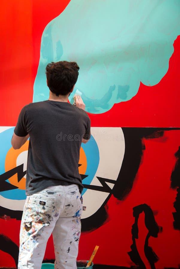 Een kunstenaar die een muurschildering schilderen stock foto's
