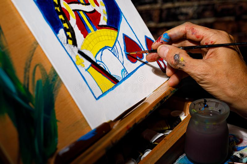 Een kunstenaar die een Koningin van Hartenspeelkaart schilderen op een canvas in hun studio royalty-vrije stock afbeelding