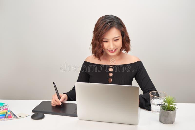 Een kunstenaarstekening iets op grafische tablet op het kantoor stock afbeelding