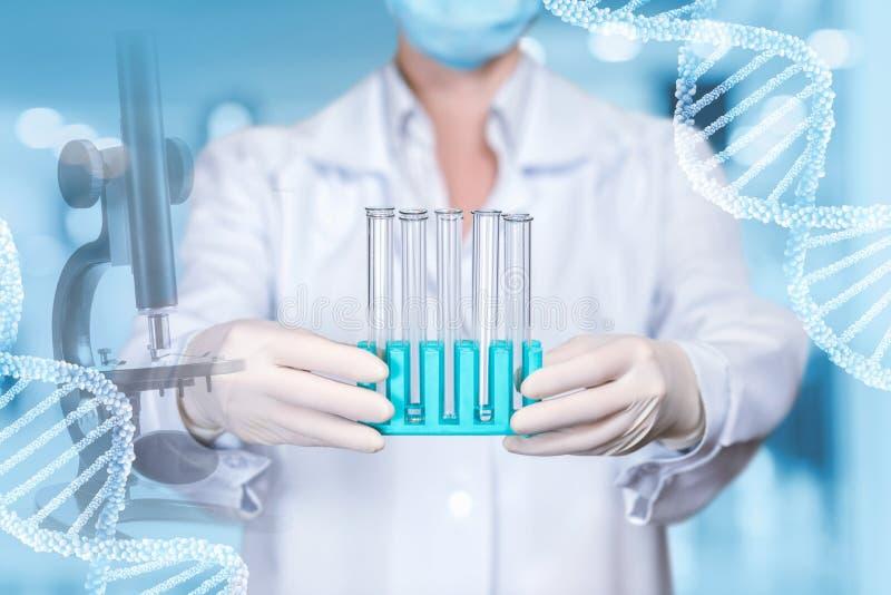 Een laboratoriummedewerker bevat een reeks reageerbuizen bij de laboratoriumachtergrond met DNA-modellen door haar kanten royalty-vrije stock afbeeldingen