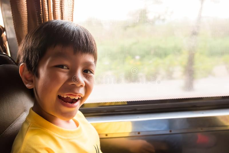 Een lachende jongen reist naar de stad door de bus van de metropool in de ochtend hij geniet van met dit vervoer, verkeers niet j stock afbeeldingen