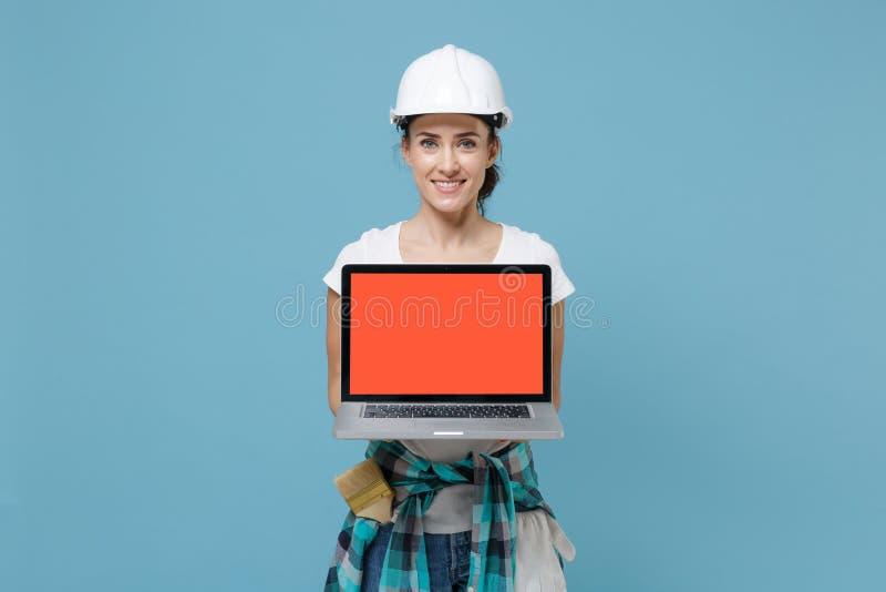 Een lachende vrouw in een beschermende helmhardt houdt een laptop-pc tegen met een leeg leeg scherm dat op een blauwe wand is geï stock fotografie