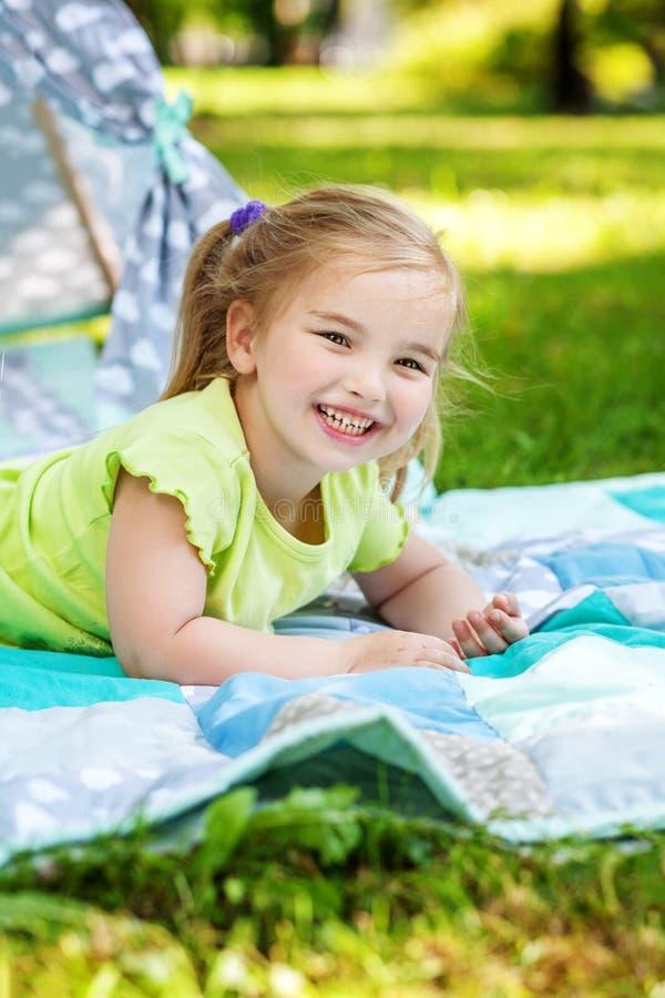 Een lacht de kleine kleuterspelen op een plaid en De zomer Concep stock afbeelding