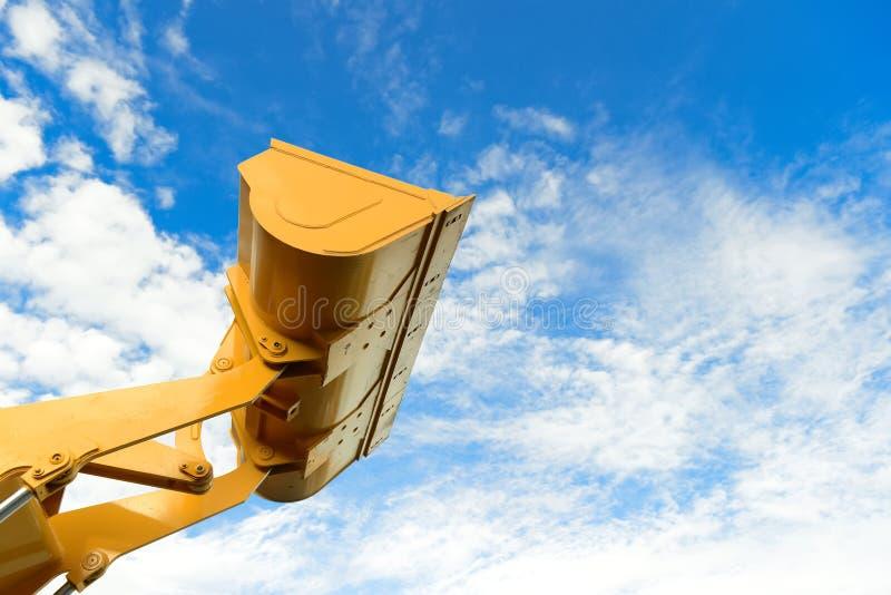Een laderdeel van de backhoe machine van de ladertractor in gele kleur met blauwe hemel op achtergrond backhoe lader terwijl binn stock foto