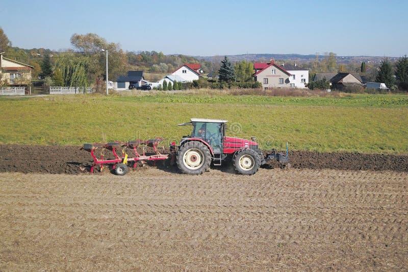 Een landbouwer op een rode tractor met een zaaimachine zaait korrel in geploegd land op een privé gebied in het dorpsgebied Mecha royalty-vrije stock foto's