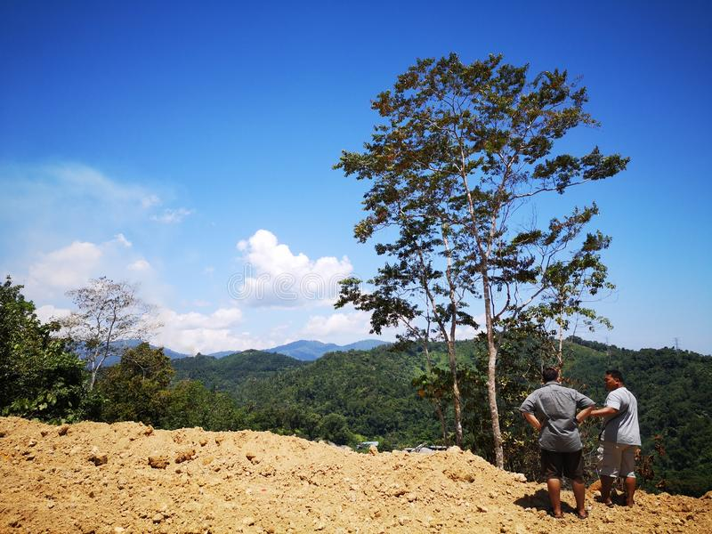 Een landmeter meet de lengte van het hoogland in Penampang, Kota Kinabalu Sabah, stock afbeeldingen