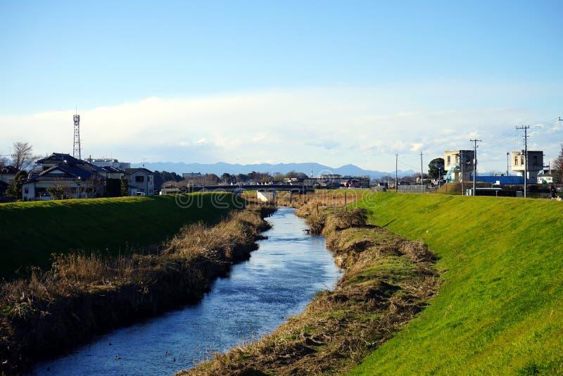 Een landschap van rivier met groene gras, plattelandshuisje, en berg als achtergrond in in de voorsteden onder de blauwe hemel stock fotografie