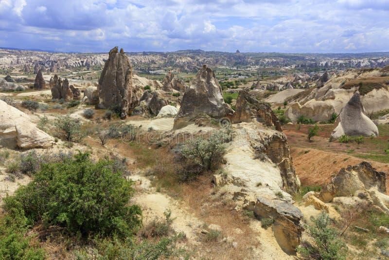 Een landweg kronkelt tussen kegelpieken van rotsen, oude holen binnen tegen de achtergrond van het berglandschap van de vallei stock foto's