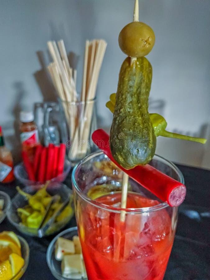 Een lange Bloody Marydrank is versierd met een schokkerig rundvlees, groenten in het zuur, banaanpeper en een groene olijf royalty-vrije stock afbeeldingen