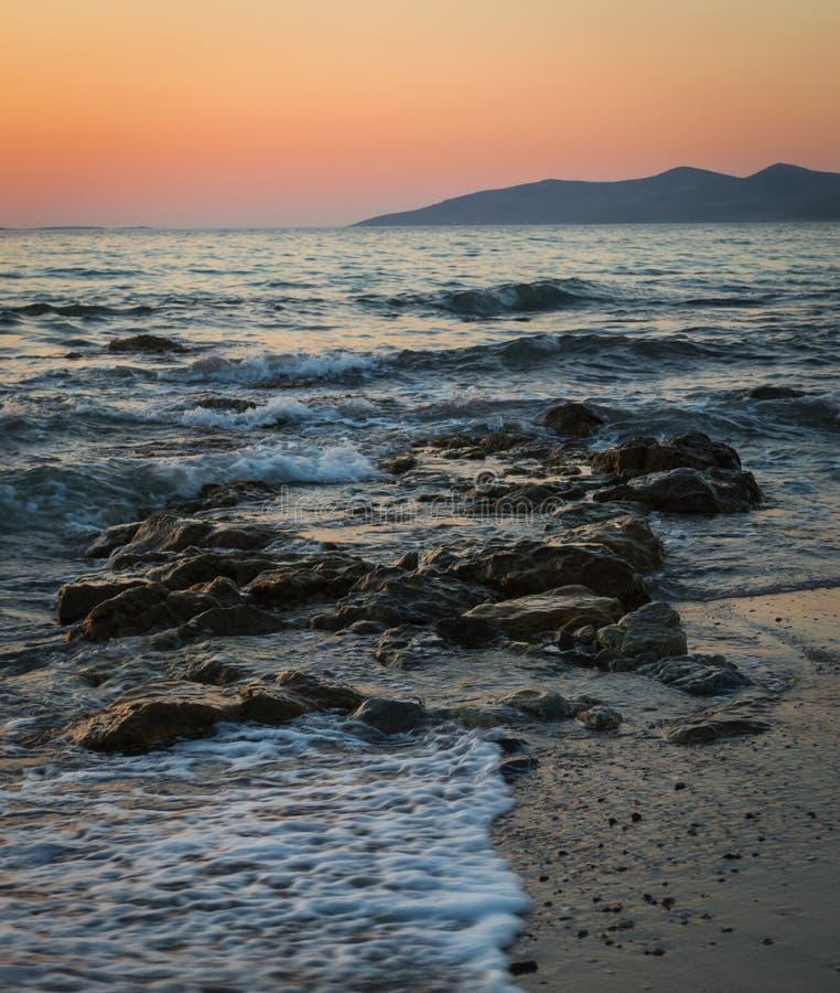 Een lange blootstelling van het overzees aangezien het over de rotsen en het strand breekt stock fotografie