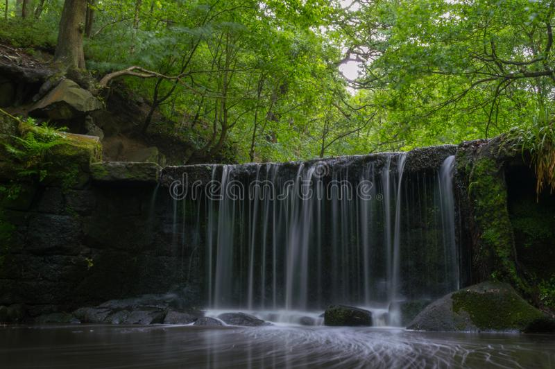 Een lange blootstelling van een kleine waterval in een afgezonderde nauwe vallei met weelderige greens en mos behandelde rotsen royalty-vrije stock fotografie