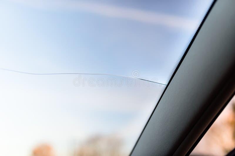 Een lange breuk van het windscherm in de auto, van de auto'spijler aan het centrum Blauwe hemel op de achtergrond stock afbeeldingen