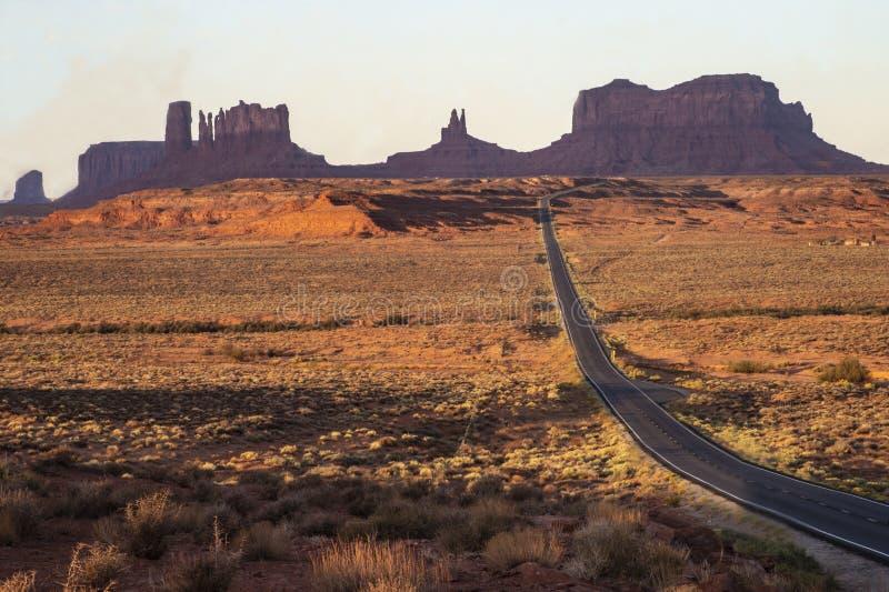 Een lange eenzame weg leidt tot pictogrammen van Monumentenvallei stock fotografie
