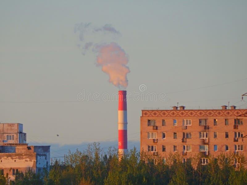Een lange industriële pijp die rookhoogte boven de stad uitzenden stock afbeelding