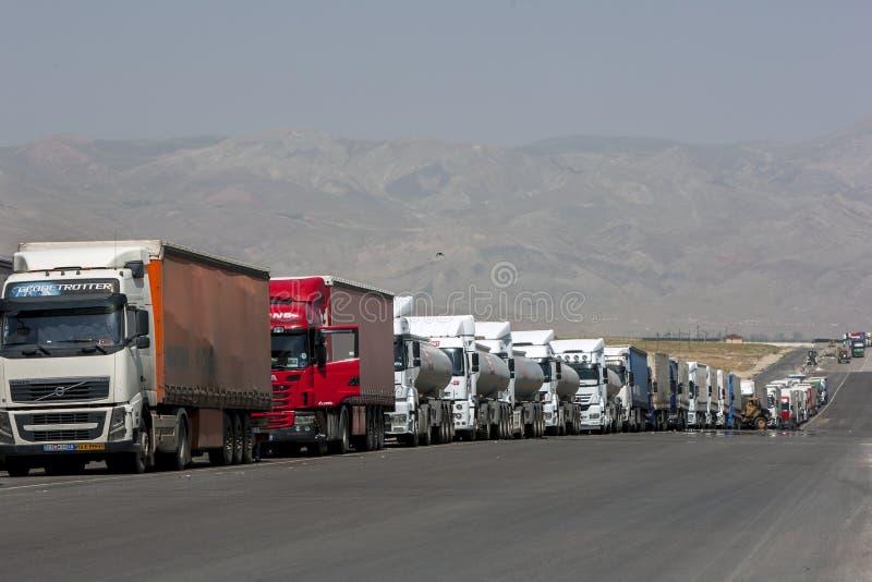 Een lange lijn van opleggers en de vrachtwagens wachten op de Turkse grens met Iran stock afbeelding