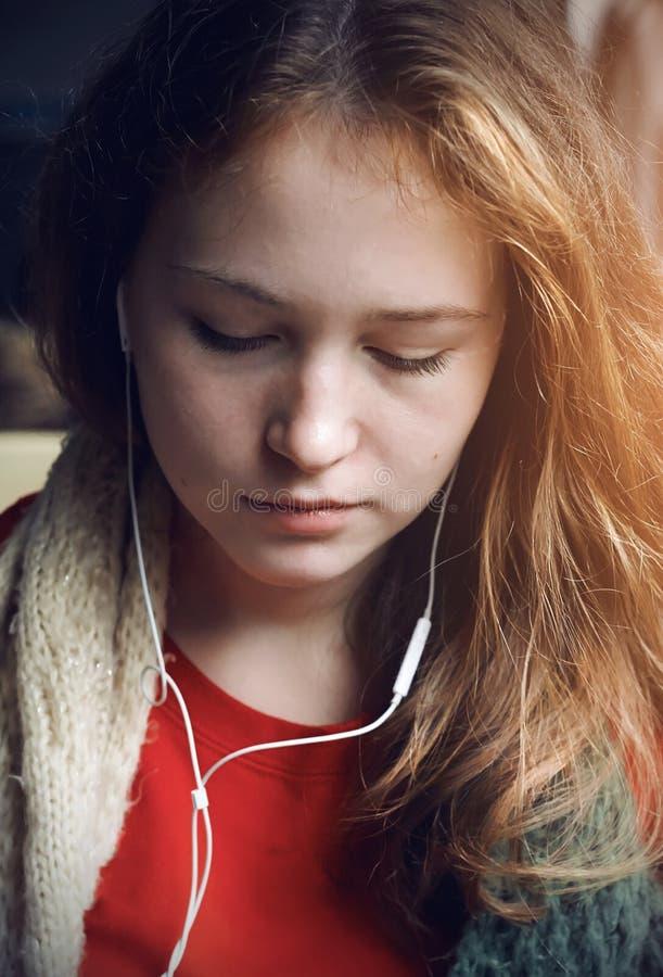 Een langharig meisje luistert aan muziek in hoofdtelefoons stock afbeeldingen