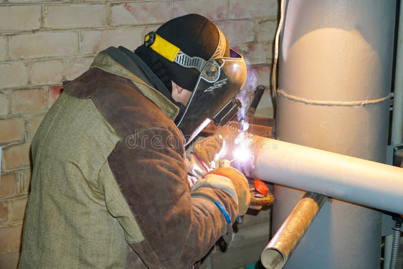 Een lasser last technologische pijpleidingen met handbooglassen voor een olieraffinaderij in Rusland Gelaste verbinding stock fotografie