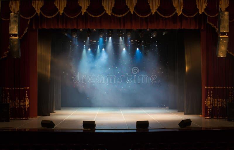Een leeg die stadium van het theater, door schijnwerpers en rook wordt aangestoken stock foto's