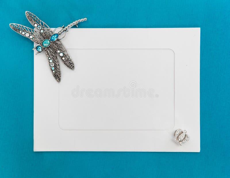 Een leeg malplaatje met Witboekkader op blauwe die achtergrond, met juwelen wordt verfraaid Zilveren libelbroche bij de hoek van stock foto