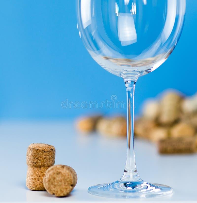 Een leeg wijnglas op een blauwe achtergrond bevindt zich op een witte lijst Kurkt van het close-up van wijnflessen Duur het proev stock afbeeldingen