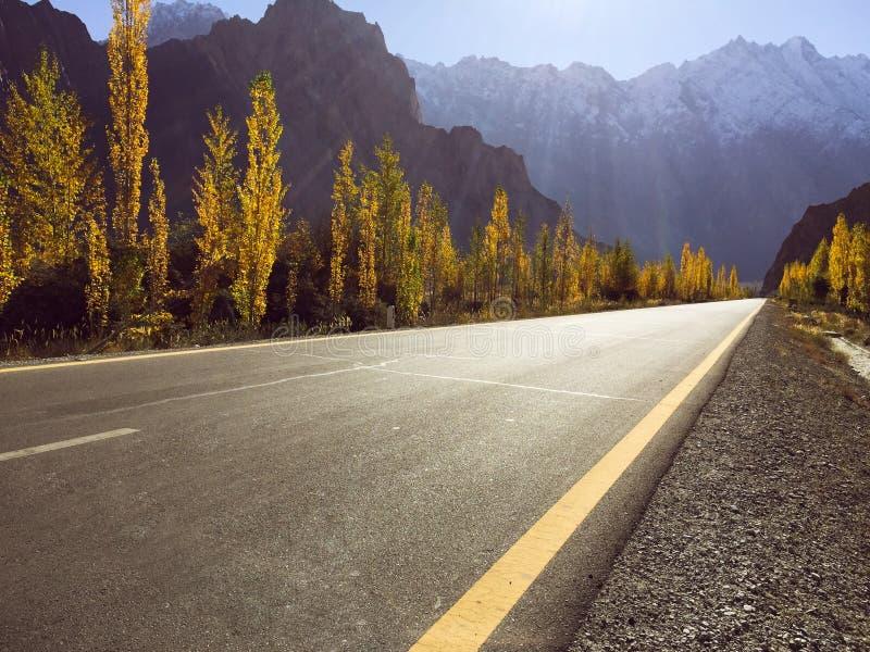 Een lege bedekte weg op Karakoram-weg tegen sneeuw dekte bergketen in de herfst af stock foto's