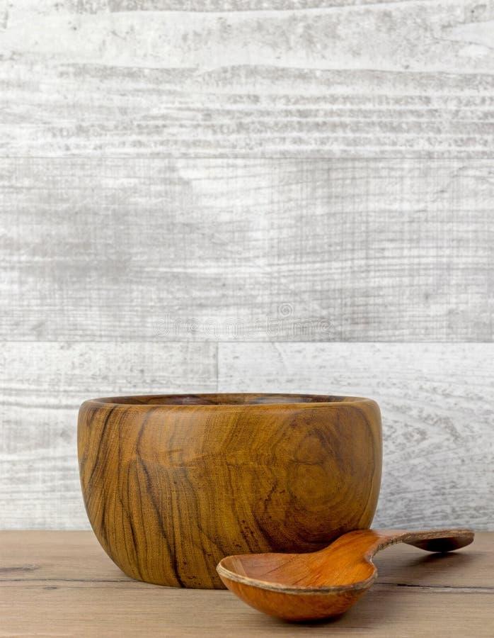 Een lege donkere houten kom en een lepel stock foto
