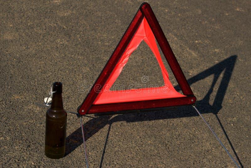 Een lege fles van bier of andere alcohol en een gevarendriehoek stock foto's
