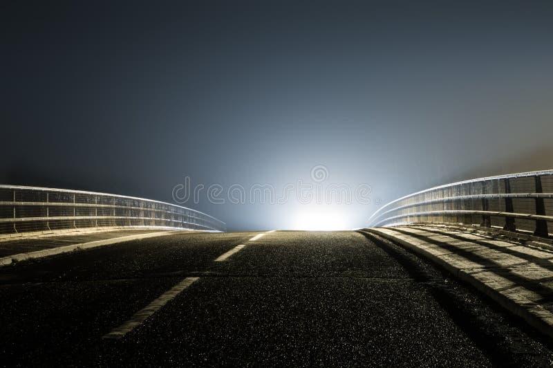 Een lege griezelige weg op een de wintersnacht met een geheimzinnige UFOgloed enkel onder de horizon stock foto's
